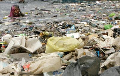 Boy swimming in a sea of plastics. Manila Bay.